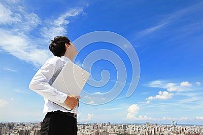 De bedrijfsmens die laptop met behulp van en kijkt aan blauwe hemel