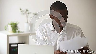 De beklemtoonde boze Afrikaanse zakenman houdt met vermoeid van moeilijke multitasking baan op stock footage