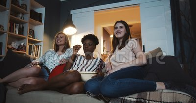 De belles et variées amies regardent une émission de télévision ensemble à la maison. Divertissement et diffusion en continu  clips vidéos