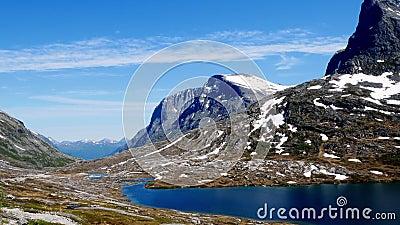 De belles montagnes de haute altitude en Norvège avec de la neige sur des pics rocheux, un lac bleu et des nuages sages dans un c clips vidéos