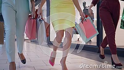 De benen van modieuze klantenvrouwen slepen op seizoengebonden kortingen in manierboutique mee en dragen partij van het winkelen  stock video