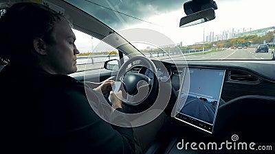 De bestuurder doorbladert zijn telefoon terwijl de auto zich langs de weg beweegt stock video