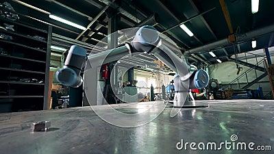 De bewegingen van het fabriekswapen, die met een toestel aan een lijst werken stock footage