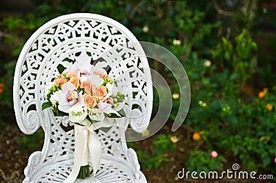 De bloemboeket van het huwelijk op een witte tuinstoel