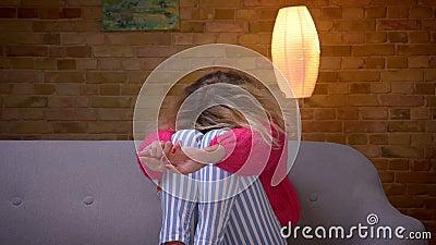 De blondehuisvrouw die in roze sweater op bank op TV letten wordt angst aangejaagd en verbergt haar gezicht bij comfortabel huis stock video