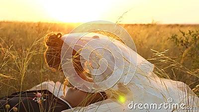 De bruid en de bruidegom bij zonsondergang rusten samen het zitten op gebied met tarwe en het glimlachen bij elkaar honeymoon min stock footage