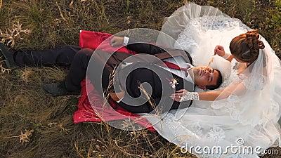 De bruid en de bruidegom bij zonsondergang rusten samen het zitten op gebied met tarwe en het glimlachen bij elkaar honeymoon min stock video