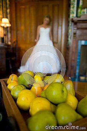 De bruid van de uit-van-nadruk achter een dienblad van peren