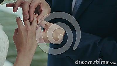 De bruidegom draagt een trouwring op de vinger van de bruid Huwelijksceremonie dichtbij het water De huwelijkshanden met ringen s stock video