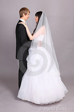 De bruidegom en de bruid omhelzen en bekijken elkaar
