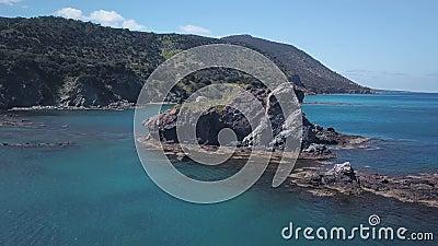 De camera vliegt rond klein rotsachtig eiland in overzees dichtbij kust, turkoois water van Middellandse-Zeegebied stock videobeelden
