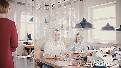 De camera volgt de aantrekkelijke vrouwelijke werkgever bureau, spreekt aan collega's, glimlacht, motiveert arbeiders in in burea stock videobeelden