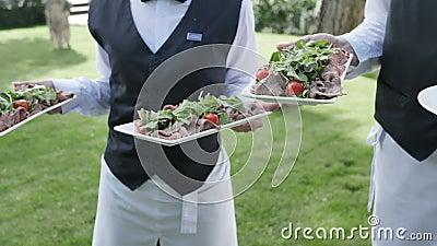 De cateringsdienst twee kelners in hun handen houdt de schotels van het de worstvlees van de tomatensalami om een langzaam huweli stock footage