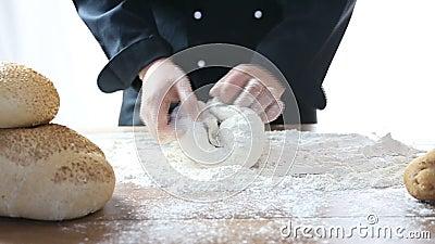De chef-kok kneedt het deeg stock footage