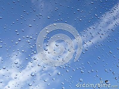 De dalingen van de regen en blauwe hemel