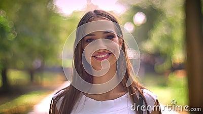 De dame van Nice bevindt zich in park in dag, lettend op bij camera, vage glimlach, backgrouns stock videobeelden