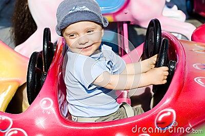 De de jongenspret van de baby op vrolijk gaat om carrousel