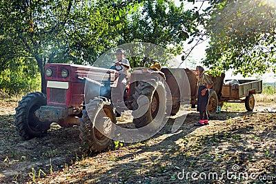 De familie van landbouwers met tractor