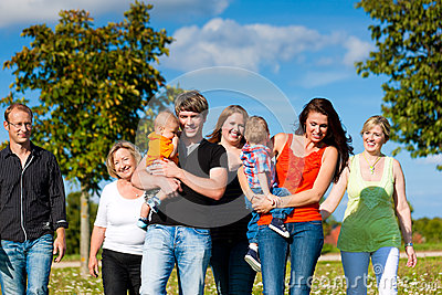 De familie van meerdere generaties op weide in de zomer