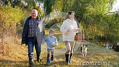 De familiegang, gelukkige grootouder met kleinzoon samen met hond gaat door bos bij de visserij naar meer bij weekend stock footage