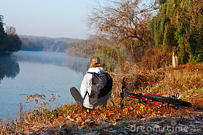De fietserrecreatie van de vrouw op de rivieroever