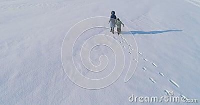 De gang en het spel van de familietijd samen Moeder en zoon die hand in hand het sneeuw behandelde gebied in de winter doornemen  stock videobeelden