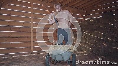 De gebaarde mens in glazen met naakt torso zet op bretels Knappe kerel die zich dichtbij kruiwagen met hooi in de koude bevindt stock video