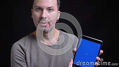 De geconcentreerde Kaukasische mens op middelbare leeftijd met oorring het letten ernstig op in tablet toont het zijn blauw scher stock footage