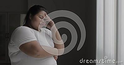 De gefrustreerde te zware vrouw bevindt zich dichtbij venster stock footage