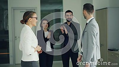 De gelukkige kerel in kostuum krijgt baan in bedrijf na succesvol gesprek, schudt handen en glimlacht uitdrukkend opwinding stock footage