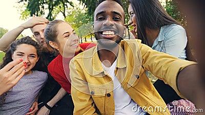 De gelukkige vrienden maken online videovraag bekijkend camera, sprekend en lachend terwijl de Afrikaanse Amerikaanse mens houdt