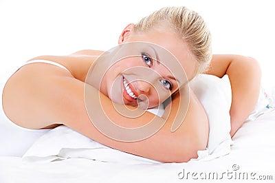 De gelukkige vrouw omhelst het witte hoofdkussen