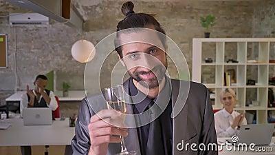 De gelukkige zakenman met baard bevindt zich en houdend glas champagne in bureau, slaan de collega's, bedrijf stock footage