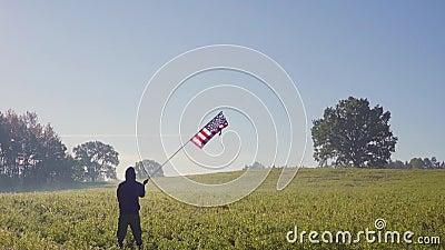 De gesilhouetteerde die mens, door zon wordt aangestoken, tribunes op kei, houdt Amerikaanse vlag die golven stock videobeelden
