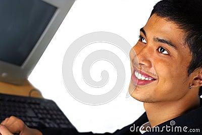 De glimlach van de mens bij voorzijde van computer