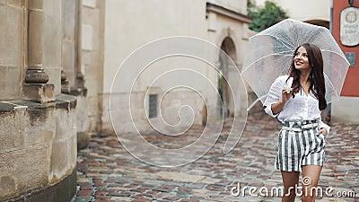 De glimlachende jonge donkerbruine vrouw in kleding loopt met paraplu langs de straat van een oude stad Het lopen onder de regen stock footage