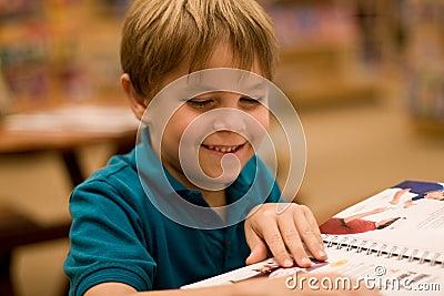 De glimlachende jongen leest een boek bij bibliotheek