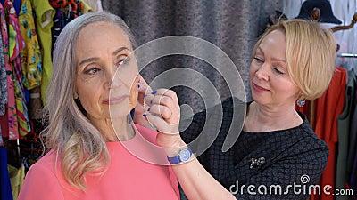 De grijze haired hogere vrouw die oorringen in toebehoren probeert slaat en aan spiegel kijkt op Verkoper die veer helpen te kiez stock videobeelden