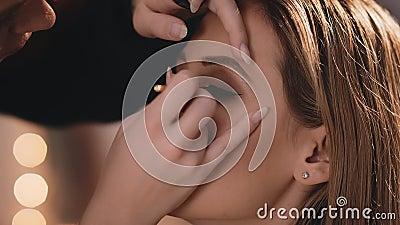 De grimeur houdt het model met zijn hand en zet zacht een zwarte eyeliner op de oogleden van zijn ogen, met a stock footage