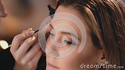 De grimeur past zacht een zwarte natte eyeliner op de oogleden, met een professionele borstel op het gezicht van mooi toe stock footage