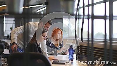 De groep van bedrijfs mensen heeft vergadering en werkt in modern, helder bureau binnenshuis stock video