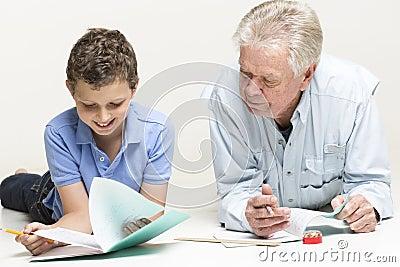 De grootvader helpt zijn kleinzoon met thuiswerk