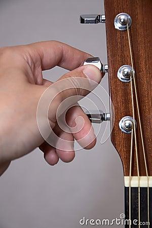 De hand die van de gitarist akoestische gitaar stemt