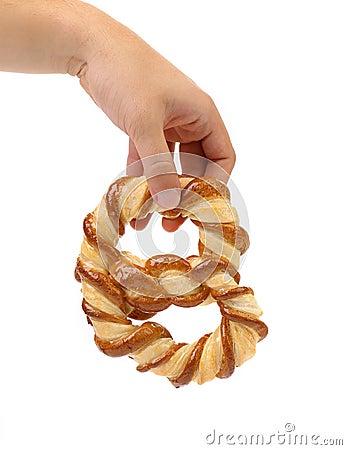 De hand houdt vers buitensporige pretzel gebakken.