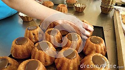 De hand van de bakkerij die de cupjes uit schimmels haalt stock videobeelden