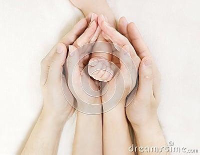 De hand van de baby binnen de handen van de ouder