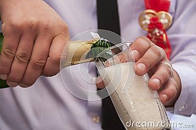 De handen gieten champagne