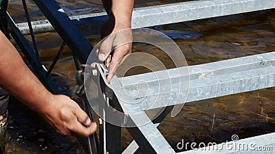 De handen van een mens halen een bout en een noot aan gebruikend een regelbare toenemende moersleutel en een combinatiemoersleute stock videobeelden