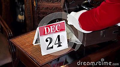 De handen van de kerstman veranderen de kalenderpagina in 24 van December De Kerstman schakelt op de oude recorder in xmas dagen stock videobeelden