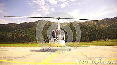 De helikopter bereidt de start voor, de piloot sluit de deur Kleine lichte luchtvaart onderaanzicht op een propeller stock videobeelden